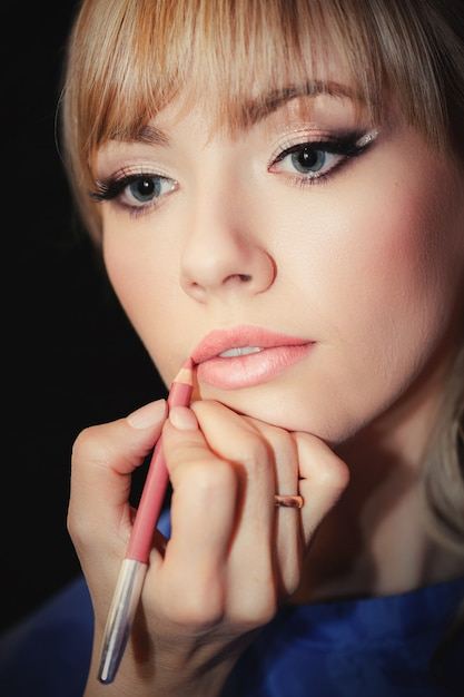 Young beautiful girl is applying make up by make up artist close up Premium Photo