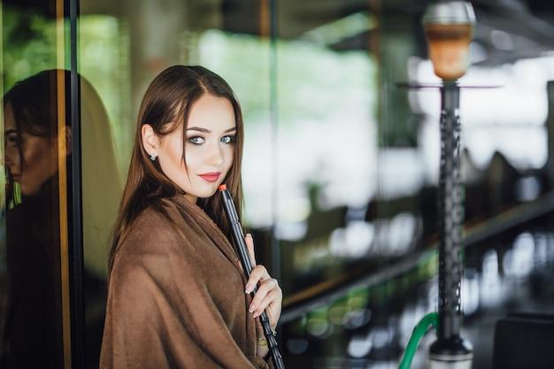 Молодая красивая девушка накрывается одеялом, стоит и курит кальян на летней террасе современного ресторана. одет в маленькое черное платье. Premium Фотографии