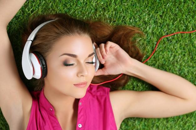 音楽を聴いて公園の芝生の上に敷設美しい少女。夏とレジャーのコンセプトです。上面図。 Premium写真