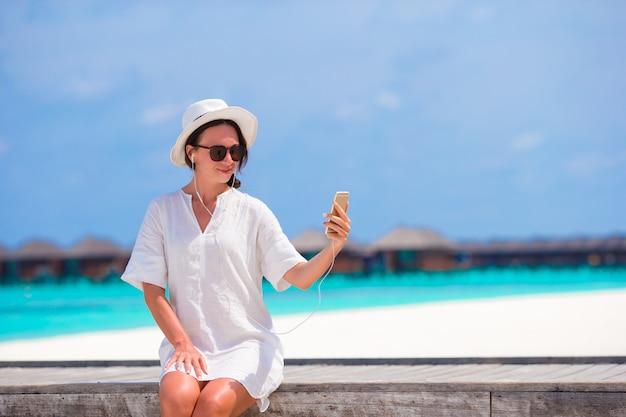 Young beautiful girl listening music on wooden bridge Premium Photo