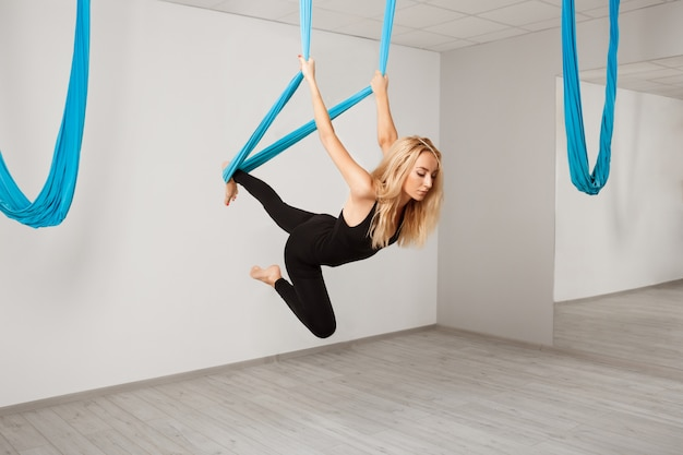 Young beautiful girl practicing aerial yoga in gym. Free Photo