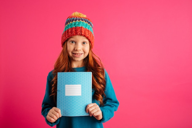 Young beautiful girl showing blue copy book and smiling isolated Free Photo