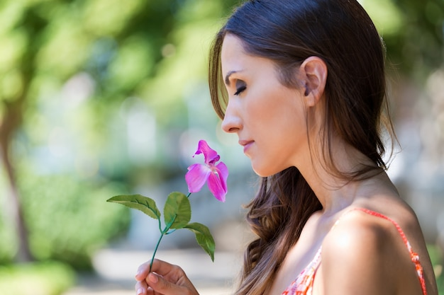 Young beautiful girl smells flowers, against green summer garden. Free Photo
