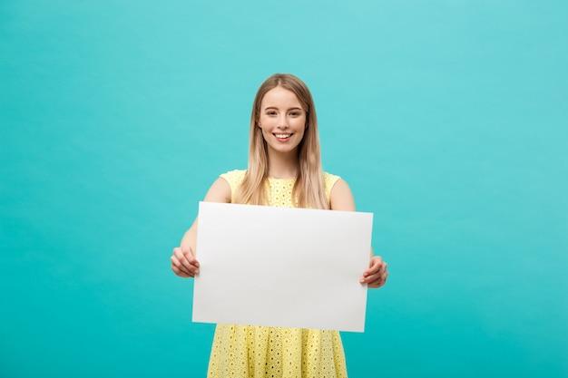 若い、美しい、女の子、笑顔、紙、白、黄色、身に着けている Premium写真