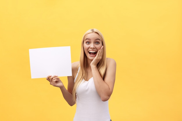 Young beautiful girl smiling and holding a blank sheet of paper, isolated on pastel yellow background. Premium Photo