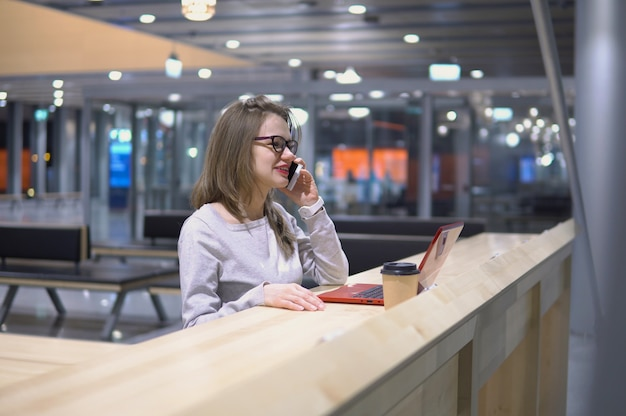 Young, beautiful girl talking on the phone standing at a table with a laptop and a cup of coffee at the airport Premium Photo