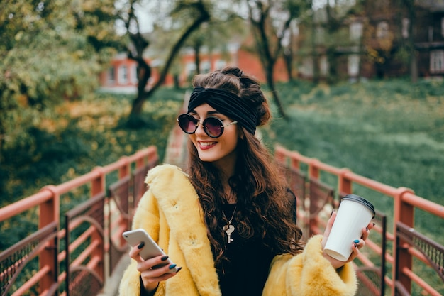 Young beautiful girl uses a smartphone on the street, surfing in the internet and drinking coffee Free Photo