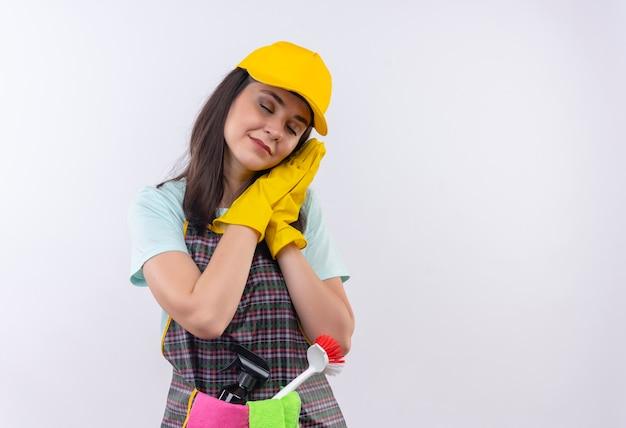 Giovane bella ragazza che indossa grembiule, berretto e guanti di gomma che tengono i palmi insieme appoggiando la testa sui palmi vuole dormire Foto Gratuite