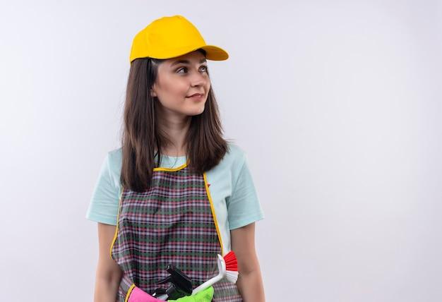 Grembiule da portare della giovane bella ragazza, berretto e guanti di gomma che osserva da parte con un sorriso sicuro Foto Gratuite