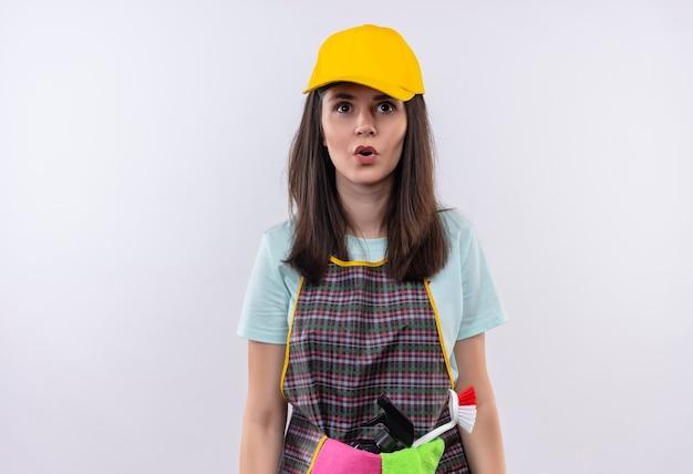 Giovane bella ragazza che indossa grembiule, berretto e guanti di gomma che guarda l'obbiettivo sorpreso Foto Gratuite