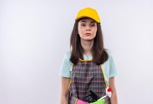 Giovane bella ragazza che indossa grembiule, berretto e guanti di gomma che guarda l'obbiettivo con seria espressione fiduciosa sul viso Foto Gratuite