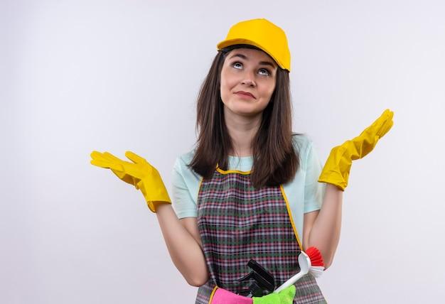 Giovane bella ragazza che indossa grembiule, berretto e guanti di gomma, alzando lo sguardo confuso diffondendo le braccia ai lati Foto Gratuite