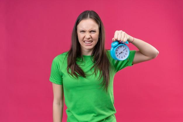 孤立したピンクの背景の上に立って怒っている渋面でカメラ目線の目覚まし時計を保持している緑のtシャツを着ている美しい少女 無料写真