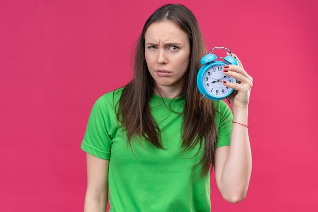 Young beautiful girl wearing green t-shirt holding alarm clock looking at camera with skeptic expression on face standing over isolated pink background Free Photo