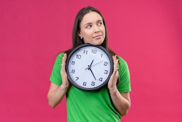 Молодая красивая девушка в зеленой футболке держит часы, глядя в сторону с мечтательным взглядом, улыбаясь, стоя на изолированном розовом фоне Бесплатные Фотографии