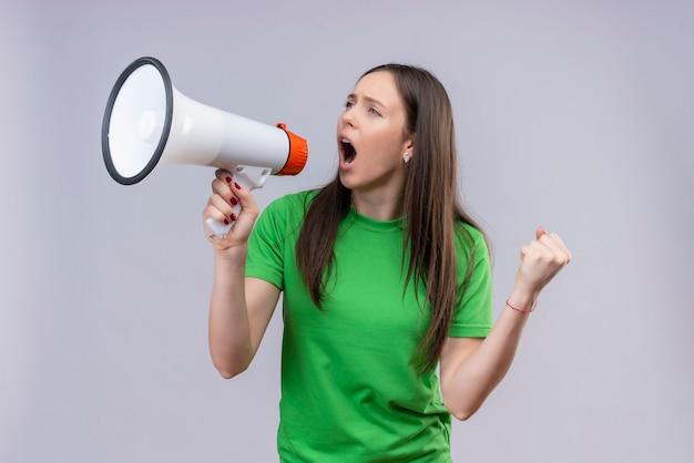 Молодая красивая девушка в зеленой футболке кричит в мегафон, эмоционально и взволнованно стоя на изолированном белом фоне Бесплатные Фотографии