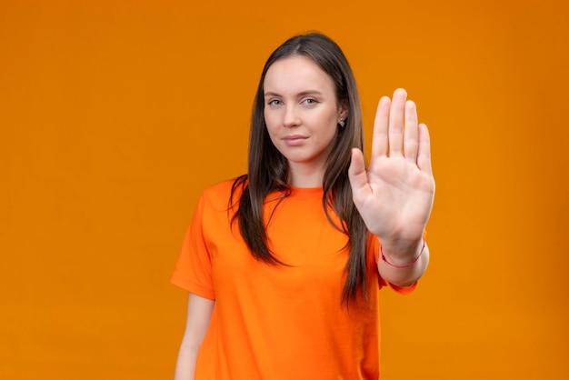 Молодая красивая девушка в оранжевой футболке стоит с открытой рукой, делая жест стоп, стоя на изолированном оранжевом фоне Бесплатные Фотографии