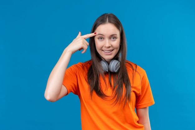 寺院を指しているヘッドフォンでオレンジ色のtシャツを着ている美しい少女 無料写真