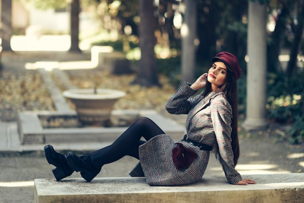 Young beautiful girl wearing winter coat and cap sitting on a bench in urban park. Premium Photo