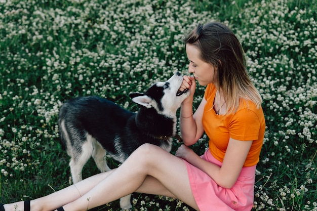 A young beautiful girl with blond hair is sitting in the meadow with her pet puppy husky and frolicking. Premium Photo