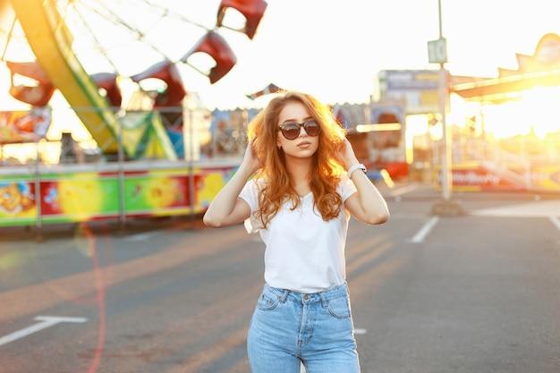 日没の夏の日に遊園地に立っている真っ赤な髪の少女 Premium写真