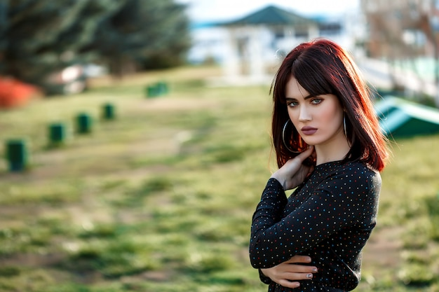 Young beautiful girl with heavy and sullen look in black dress outside posing during sunset Premium Photo
