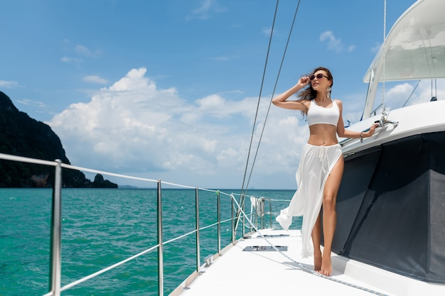 Young beautiful girl with long hair standing bow the yacht in white skirt and bikini. Premium Photo