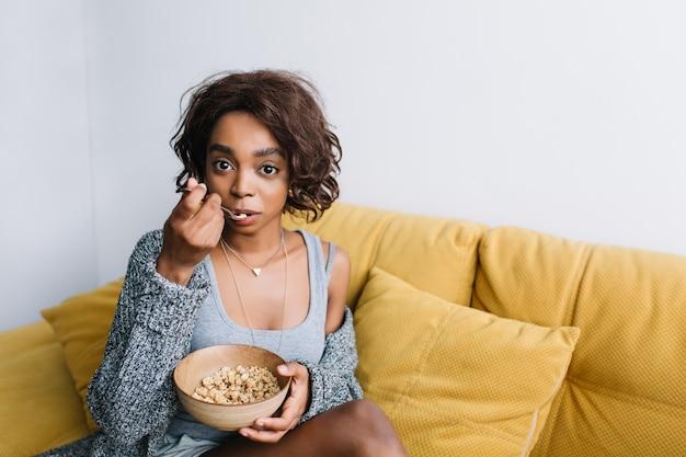 Молодая красивая девушка с короткими вьющимися волосами, имеющими здоровый завтрак, едят мюсли, мюсли на желтом диване, софе. атмосфера домашнего утра. одет в серый кардиган, майку. Бесплатные Фотографии