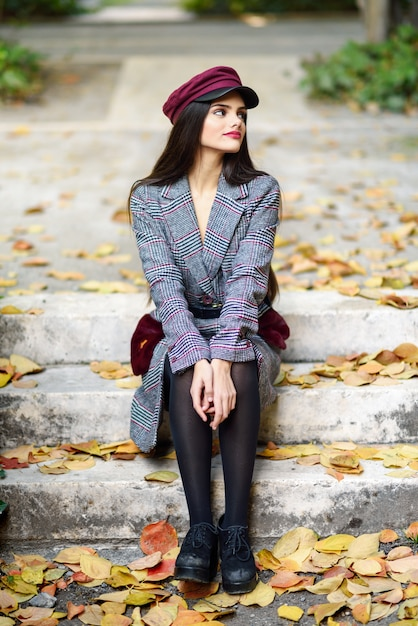 Young beautiful girl with very long hair wearing winter coat and cap in autumn leaves Premium Photo