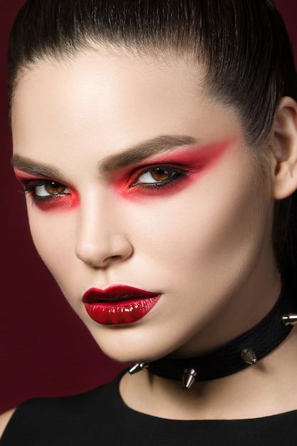 Молодая красивая готическая женщина с белой кожей и красными губами с кровавыми каплями носит черный воротник с шипами. красные дымчатые глаза. Premium Фотографии