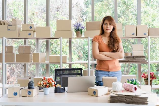 Young beautiful happy asian successful business woman with smiley face is standing with arms crossed at her startup home office, woman in good feeling with business success, delivery seller concept Premium Photo