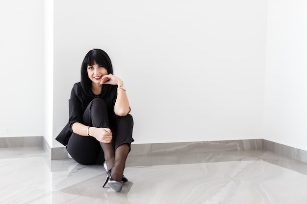 Young beautiful happy brunette woman dressed in a black business suit sitting on a floor in office Premium Photo