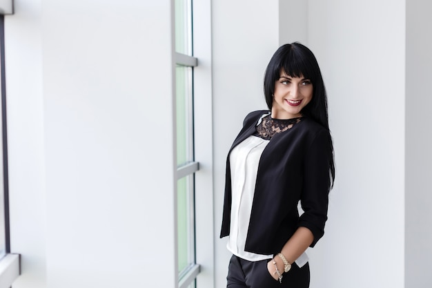 Young beautiful happy brunette woman dressed in a black business suit Premium Photo