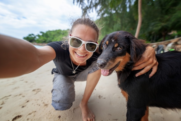 Young beautiful happy joyful girl woman having fun taking a selfie on a mobile phone with her dog on the beach along the sand Premium Photo