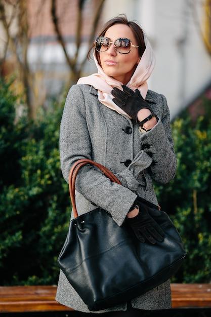 Giovane bella donna felice in un cappotto che propone al parco Foto Gratuite
