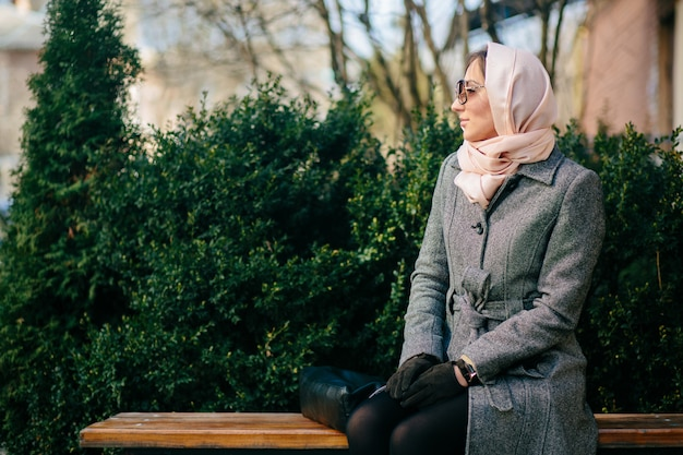 Giovane bella donna felice in un cappotto seduto su una panchina nel parco Foto Gratuite