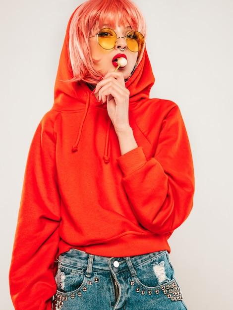 Плохая девушка молодой красивый битник в модный красный летний красный балахон и серьги в носу. сексуальная беззаботная женщина позирует в студии на сером фоне в парике. горячая модель, облизывая круглые конфеты сахара Бесплатные Фотографии