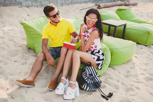 ビーチに座って、音楽を聴いて、サングラス、スタイリッシュな衣装、夏休み、楽しんで、笑顔、幸せ、カラフル、前向きな感情を愛する若い美しい流行に敏感なカップル 無料写真