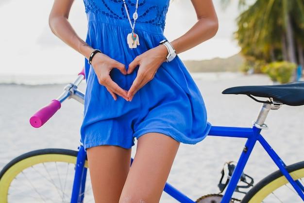 Donna giovane bella hipster in posa con la bicicletta sulla spiaggia, mostrando il cuore con le mani Foto Gratuite