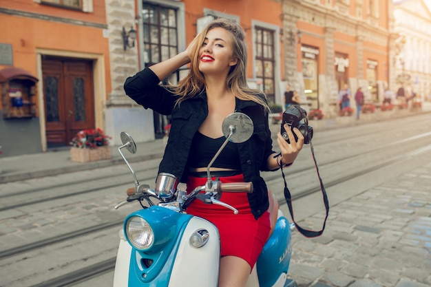Young beautiful hipster woman riding with photo camera on motorbike city street Free Photo