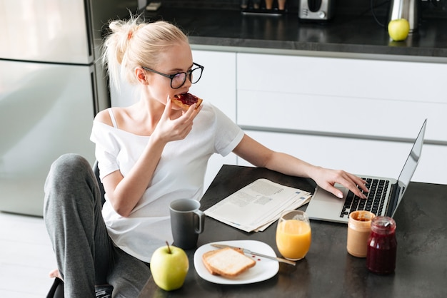 Young beautiful lady have breakfast and using laptop computer in kitchen Free Photo