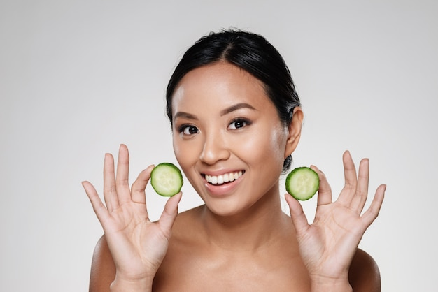 Young beautiful lady holding slices of cucumber Free Photo