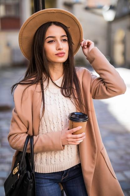 ハンドバッグと一杯のコーヒーが付いている通りに沿って歩く若い美しい女性。 無料写真