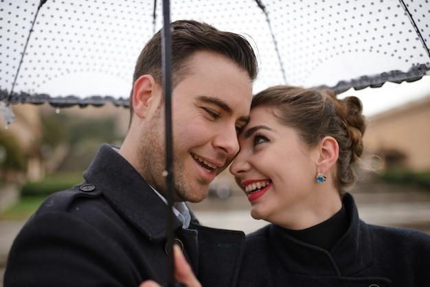 スペインのプラザで雨の中に傘の下で歩く美しい愛情のあるヒスパニックのカップル。カタルーニャ国立美術館を背景にポーズをとるカップル。 Premium写真
