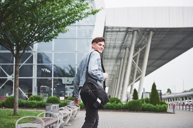 Un giovane uomo bello all'aeroporto sta aspettando il volo. Foto Gratuite