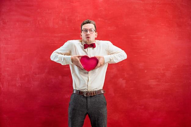 Молодой красивый человек с абстрактным сердцем на фоне красной студии Бесплатные Фотографии