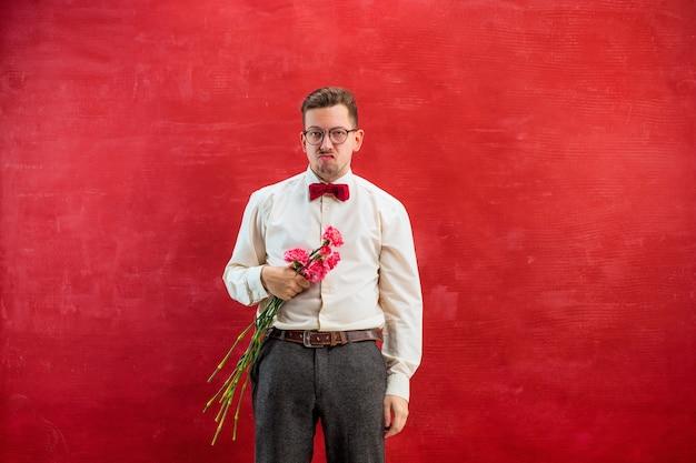 Молодой красивый мужчина с цветами на красной студии Бесплатные Фотографии