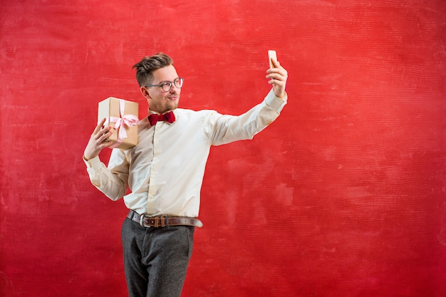 Young beautiful man with gift and phone Free Photo