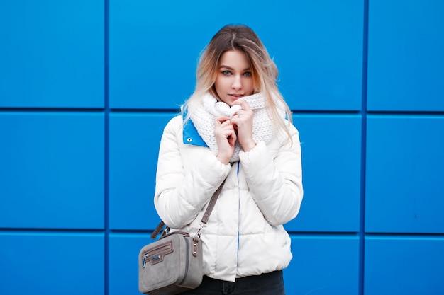 Молодая красивая модель девушка в модном вязаном шарфе и белой зимней куртке с кошельком позирует у синей стены Premium Фотографии