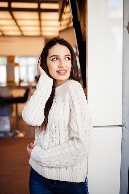 大きな目の赤い唇と長い茶色の髪を持つ若い美しいモデルは彼女の家の部屋に滞在します 無料写真